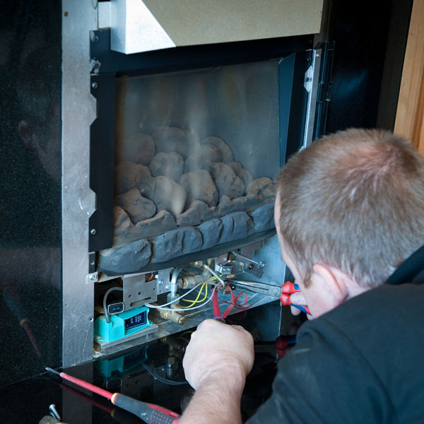 a heating contractor servicing a gas fireplace